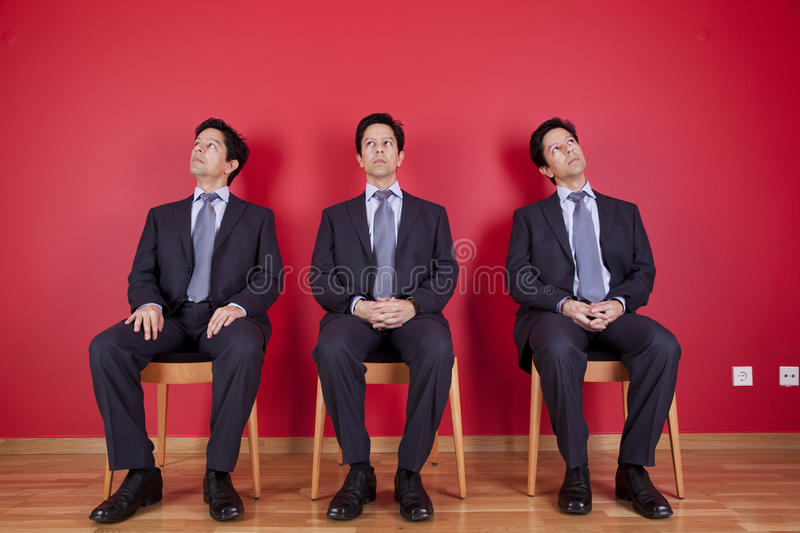 Three twin businessman waiting royalty free stock image