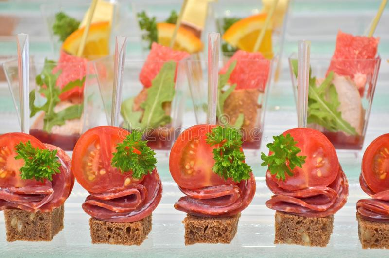 Three types of canapes with transparent and wooden skewers on a glass step support on a banquet, closeup stock images