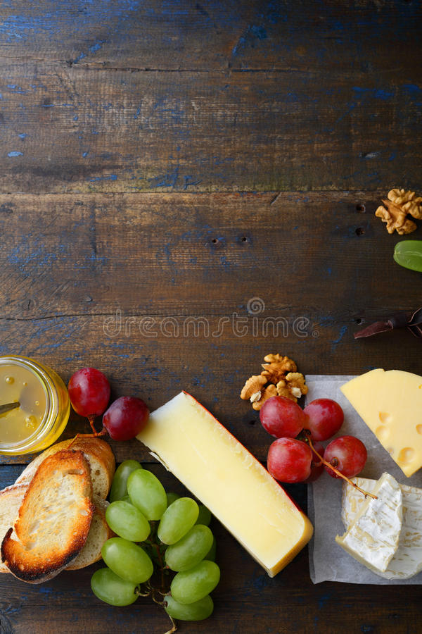 Three types of cheese with grapes, honey, bread and walnuts. Empty space background royalty free stock photos