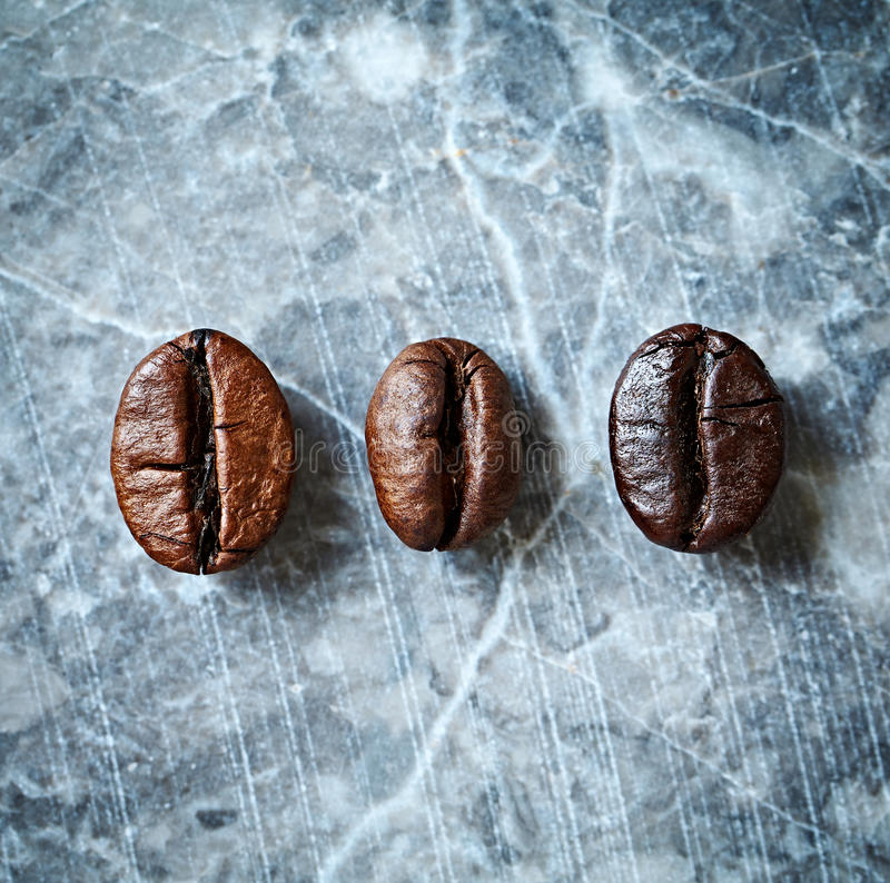 Three types of coffee beans on a marble background stock image