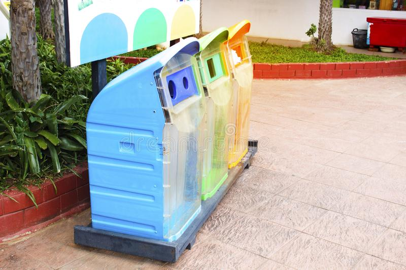 Three types of trash cans, blue, green and orange in the park royalty free stock image