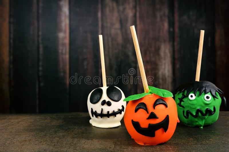 Three unique Halloween candy apples against dark wood royalty free stock photography