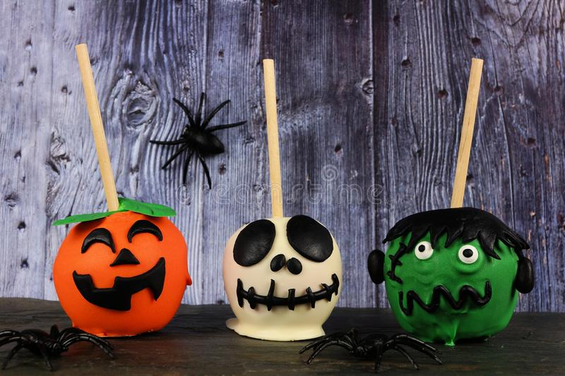 Three Halloween candy apples against a spooky wood background. Three unique Halloween candy apples against a spooky dark wood background. Jack o lantern royalty free stock image