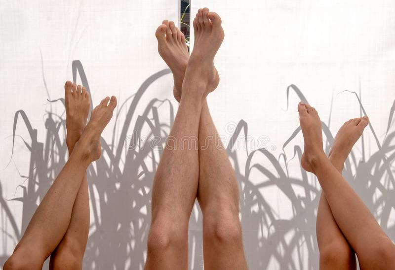 Three upturned pairs of legs in front of illuminated fabric background with shade stock photos