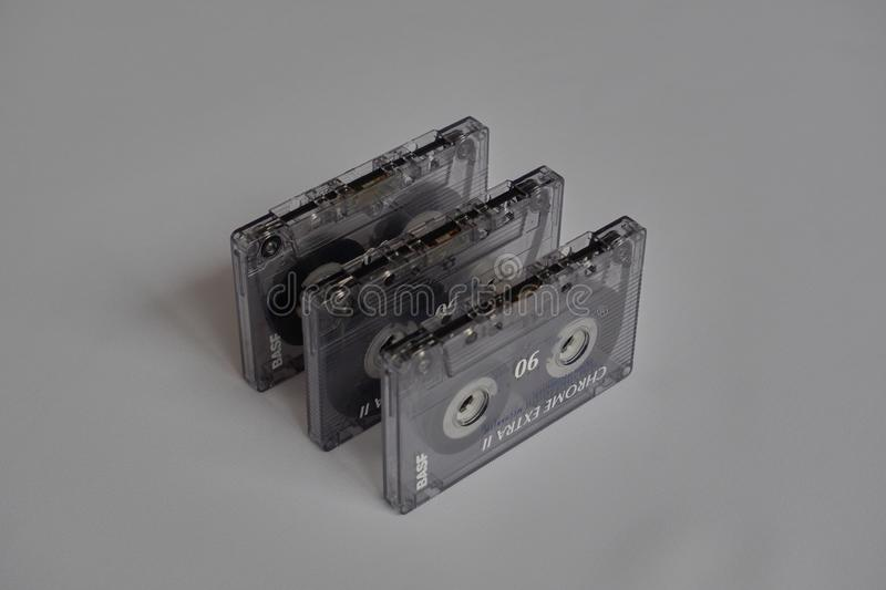 Three used vintage plastic music cassettes. Entertainment recyclable white background stock photos