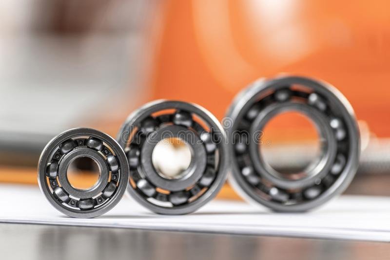 Three various ball bearings lying on paper sheet. Three various ball bearings lying on table. Automotive spare part sale company. Heavy industry engineering stock photography