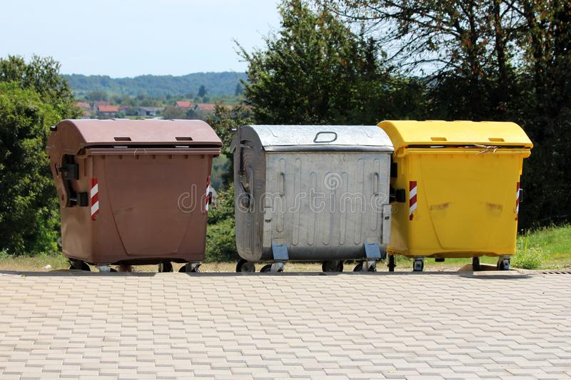 Three various large metal and plastic trash containers for ecologically sorting garbage for recycling surrounded with stone tiles stock images