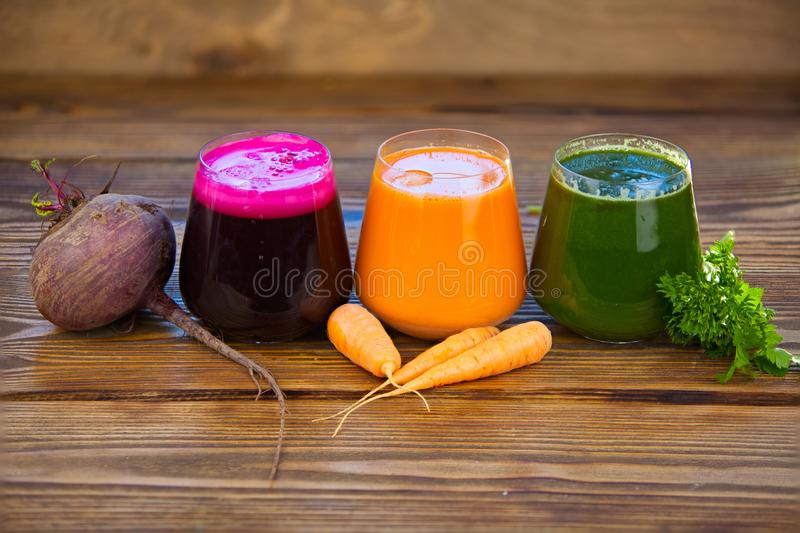 Three vegetable juice in glass cup on wooden background. Three vegetable juice in a glass cup on a wooden background royalty free stock photography