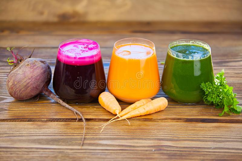 Three vegetable juice in glass cup on wooden background. Three vegetable juice in a glass cup on a wooden background stock photo