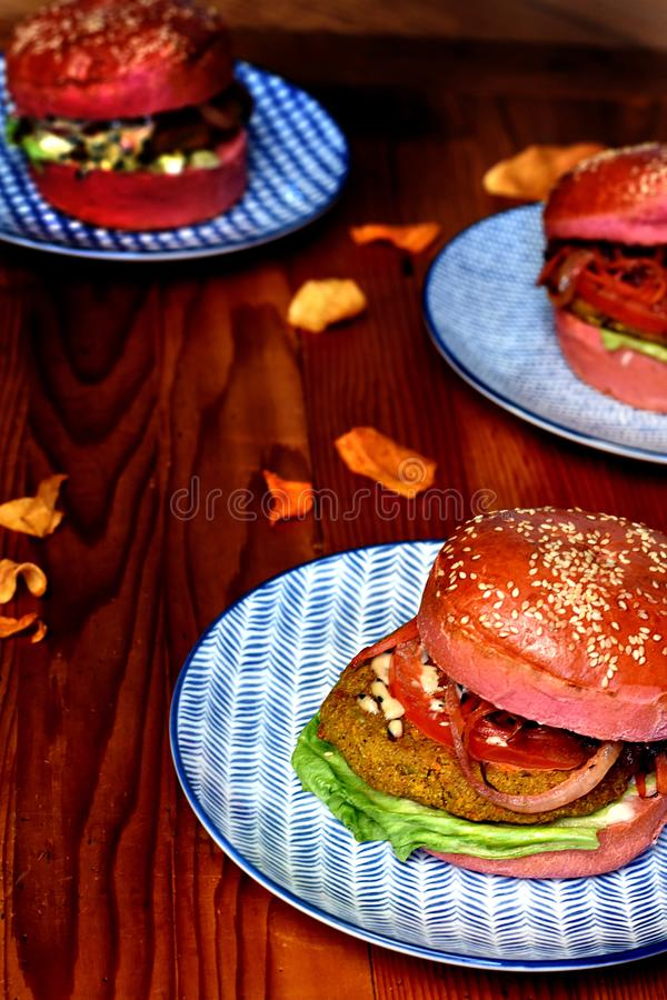Three vegetarian burgers in pink buns on blue plates stock image