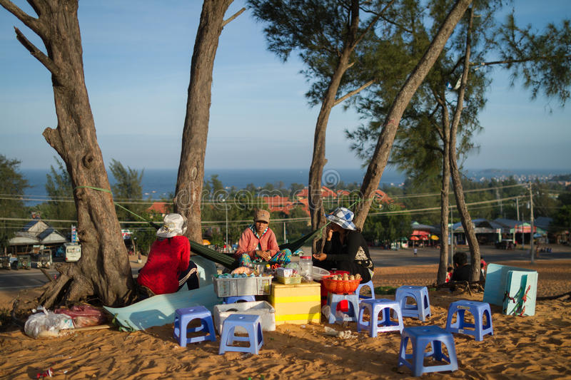 Three Vendors Sitting On A Sand Dune. Three street vendors sit on a sand dune in Mui Ne, Vietnam. The woman in an orange shirt and flowery pant sit on a hammock royalty free stock photography