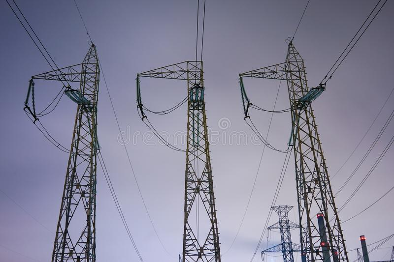 Three vertical energy structures. High tension poles, transformation point; night scene, industrial site, metallic structures, energy, 3 electric poles stock images