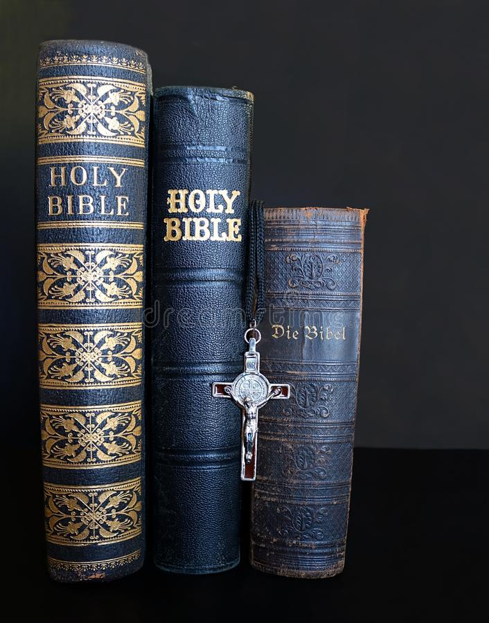 Three antique Bibles with crucifix lined up royalty free stock photo