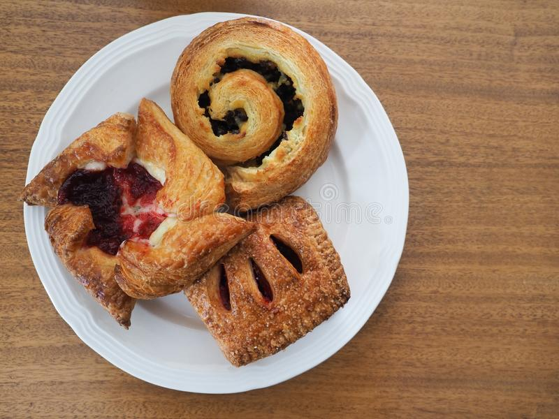 Three Viennoiserie Pastries on a White Plate. That is on a medium brown wooden table. Photographed from above royalty free stock photos