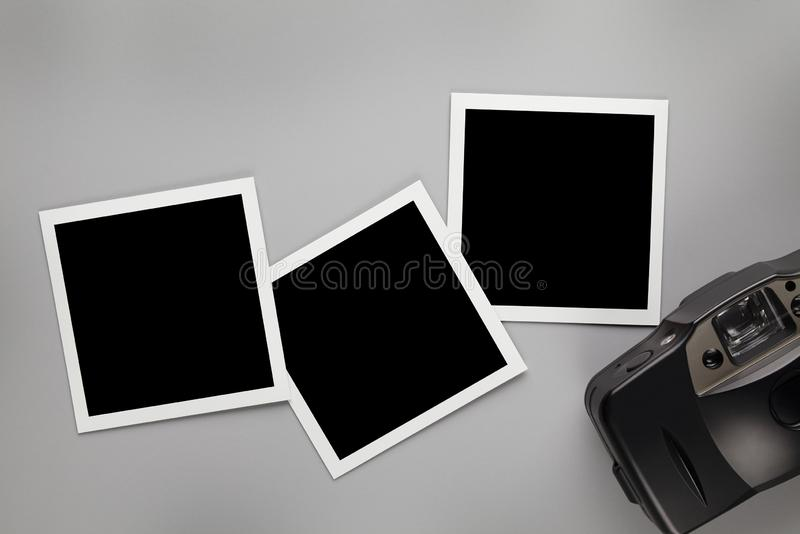 Three vintage photo frames with blank space for your content and old photo camera on gray table stock photos