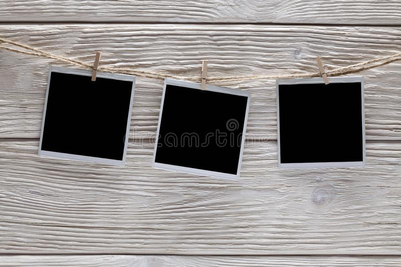 Three vintage photo frames with empty space on rope and wooden background royalty free stock photography