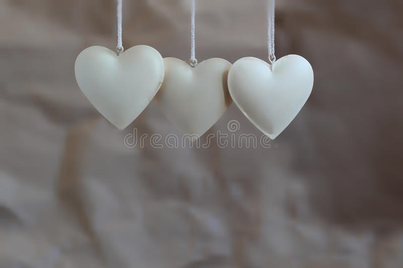 Three vintage shabby hearts on the background of old paper. Soft focus, background mode.  royalty free stock photography