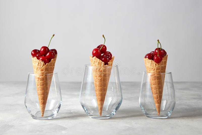 Three waffle cones with fresh ripe cherries in glasses on a gray marble table. royalty free stock image