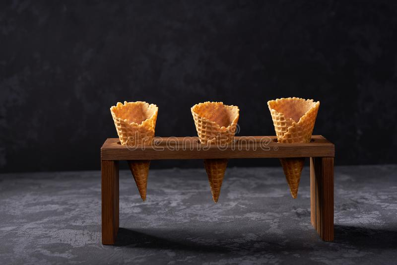 Three waffle cones waiting to be filled with ice cream on dark background. Three waffle cones waiting to be filled with ice cream selective focus scoops summer stock image
