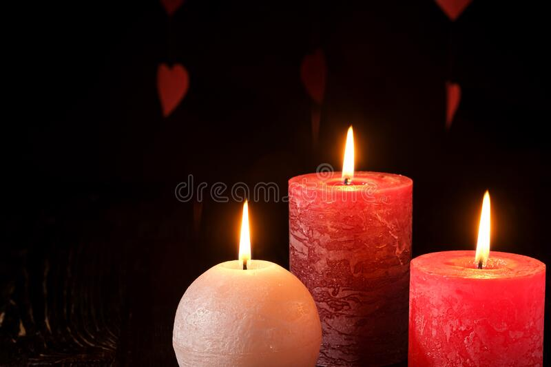 Three wax flame candlelight in dark romantic light on hearts background, love dating, Valentine`s day royalty free stock photos