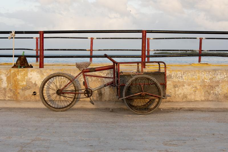 Three-wheeled bicycle. Unused three-wheeled bicycle by wall stock photo