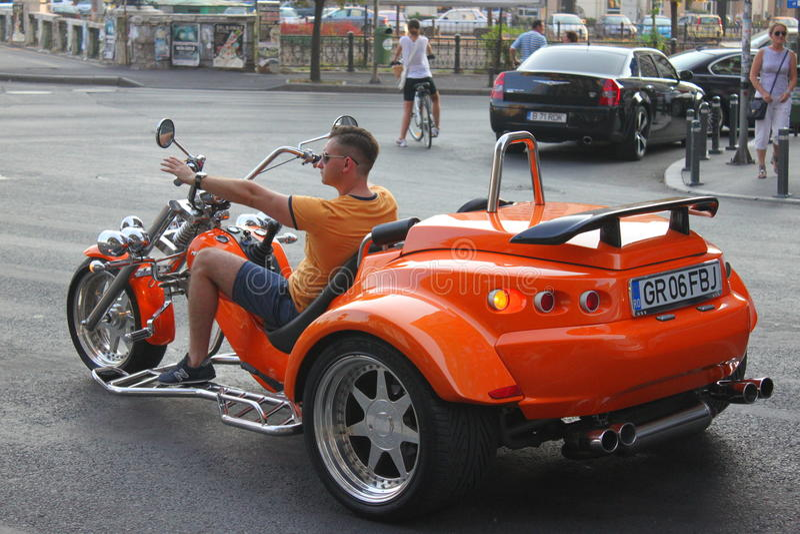 Three-wheeled motorcycle. Powerful three-wheeled motorcycle orange at traffic lights stock photography