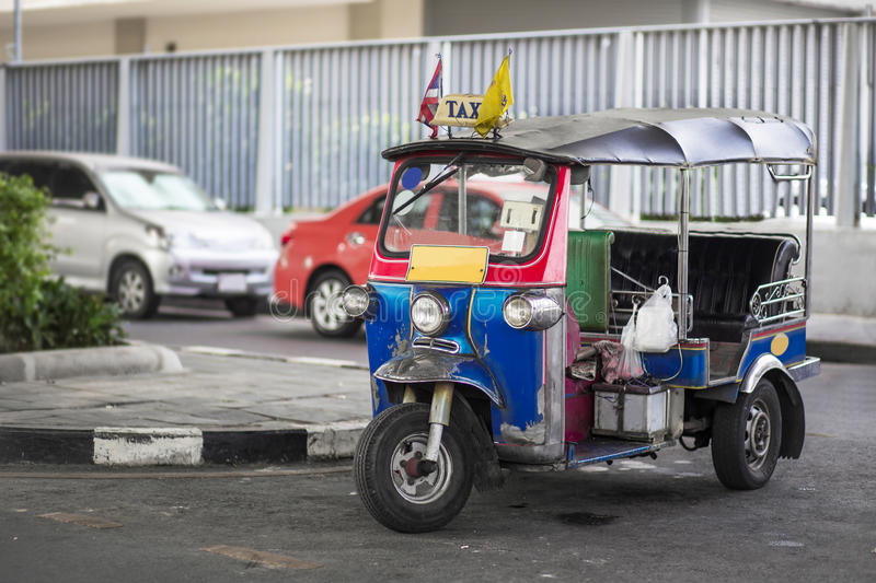 A three wheeled taxi on a street in the Thai capital. A three wheeled tuk tuk taxi on a street in the Thai capital royalty free stock photography