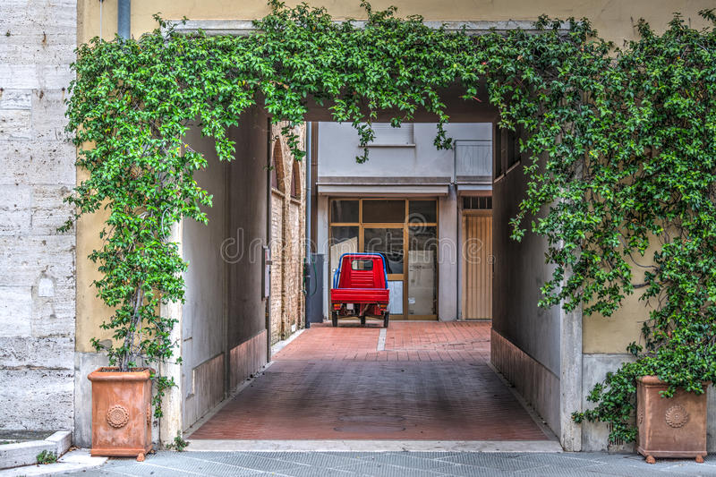 Three-wheeler car in a courtyard in Tuscany. Italy royalty free stock photos