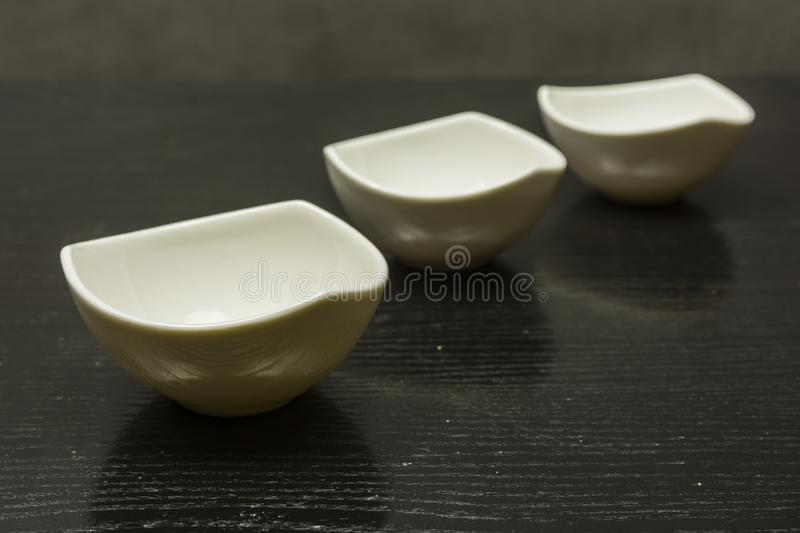 Three white bowls for sauces spread out on the table. stock images