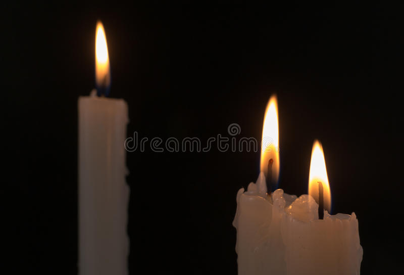 Three White Candles Burning at Night Time stock photography
