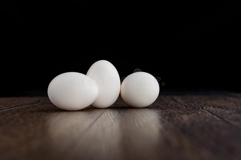 Three white chicken eggs on a wooden table royalty free stock photos