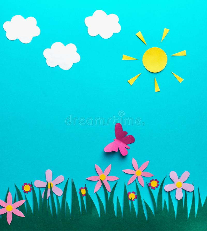 Three white clouds, grass, flowers, butterfly, summer of paper on a blue background stock photo