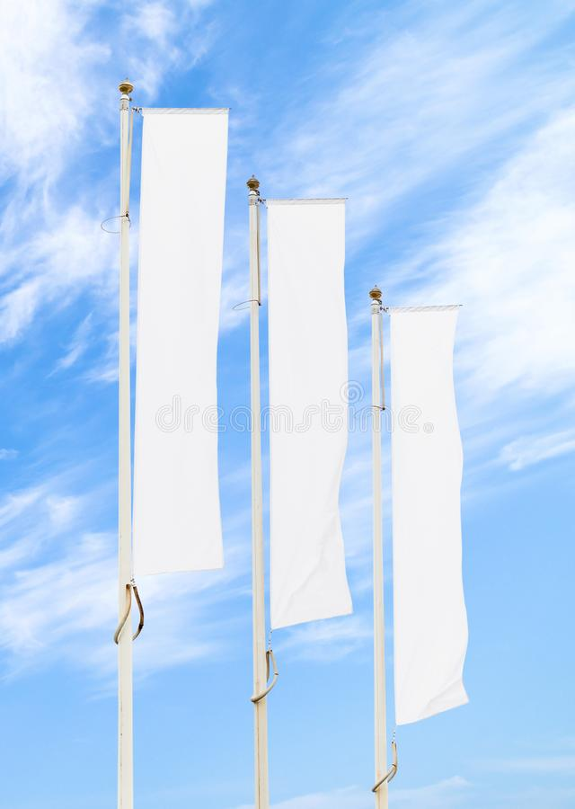 Three white corporate flags mockup against blue sky stock photography