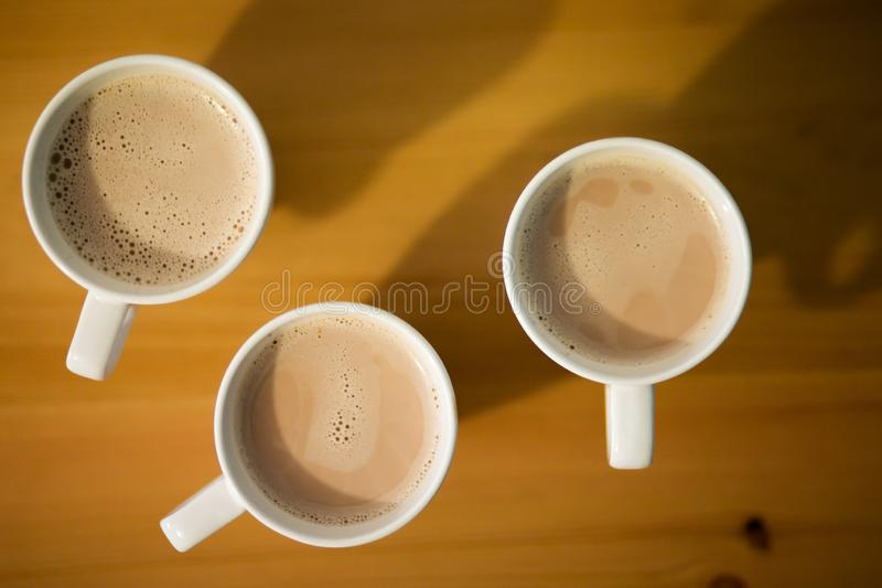 Three white cup of hot latte, coffee or cocoa on wooden table, top view, close up stock image