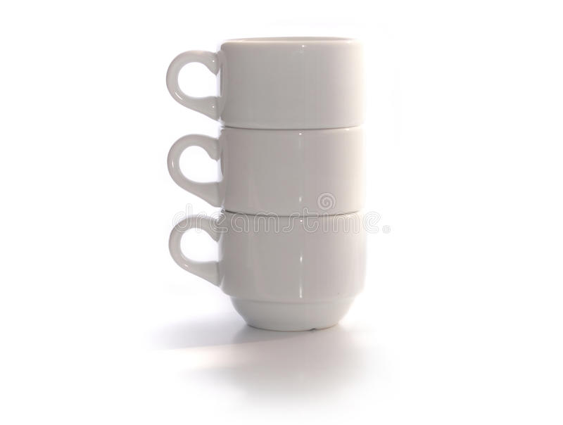 Three white cups in a pile. Three white coffee cups in a pile over white background stock photo