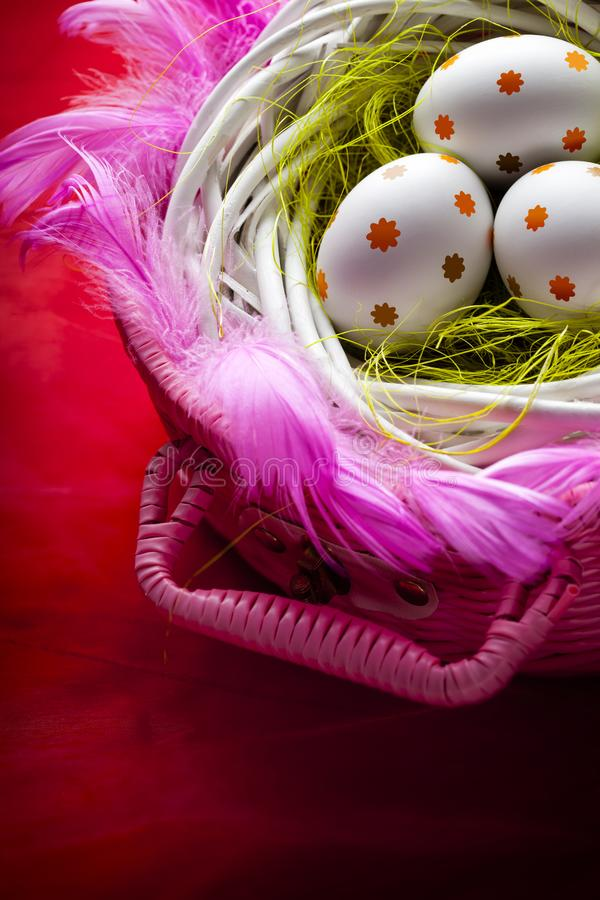 Three white Easter eggs in the nest on red background royalty free stock photo