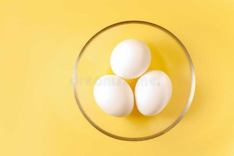 Three white eggs are lying in a round transparent glass cup in the middle of a yellow background. royalty free stock photo