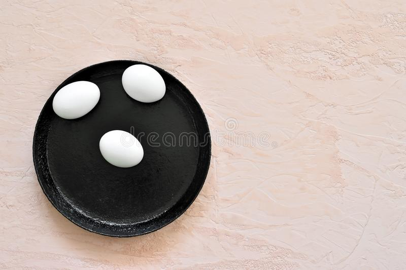 Three white eggs in a shell lie on a black pan against the background of a shade of living coral stock photos