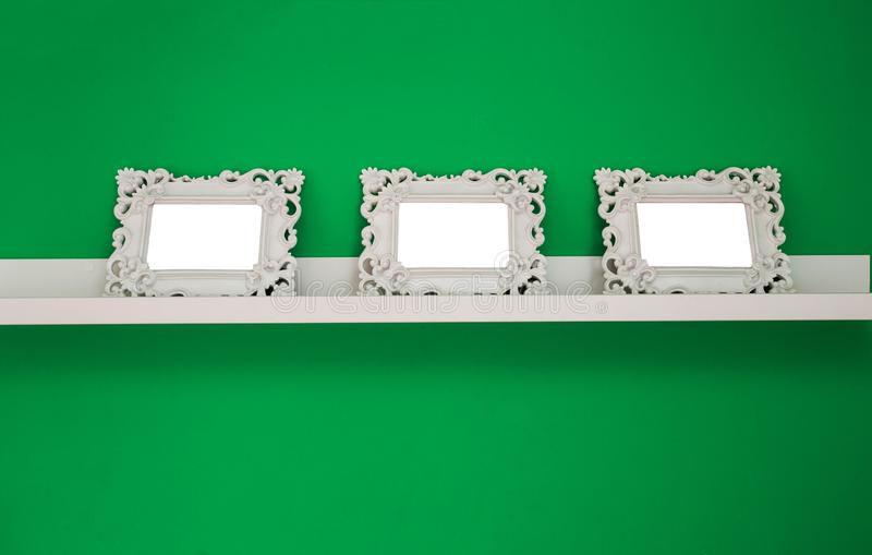Three white empty photo frames on a green wall and wooden shelf, , space for text or photo stock image
