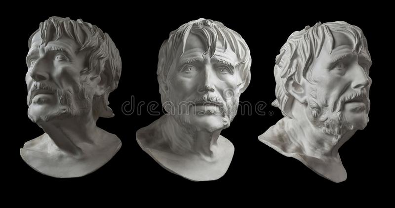 Three gypsum copy of ancient statue head of Lucius Seneca isolated on black background. Plaster sculpture aged man face. Three white gypsum copy of ancient royalty free stock photos