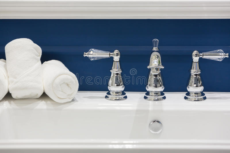 Three white hand towels on a white basin. With hot and cold faucets in a clean and classic style bathroom royalty free stock images