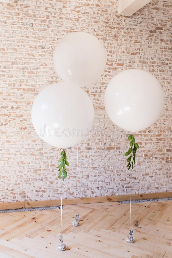 Three white huge balloons against a brick wall background royalty free stock photo