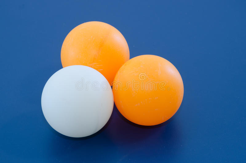 Three White and orange ping pong ball. 40mm large white and orange ping pong (table tennis) ball with blue background (raw file was provided stock images