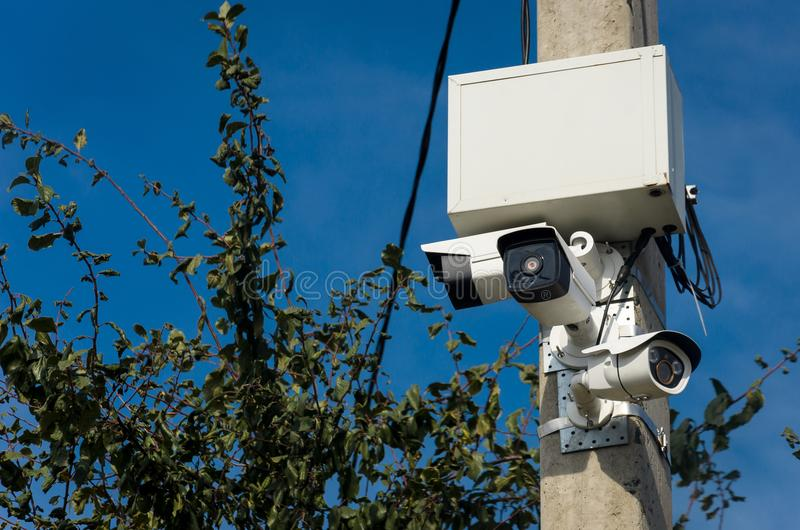 Three white outdoor CCTV cameras on the concrete pillar on the s stock photos