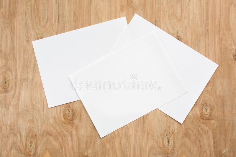 Three white sheets of paper on a wooden background.  royalty free stock photography