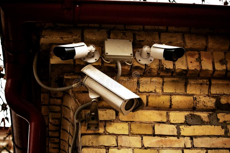 Three white video cameras on yellow brick wall. On building corner, security, safety, surveillance, technology, control, electronic, equipment, guard, modern stock photo