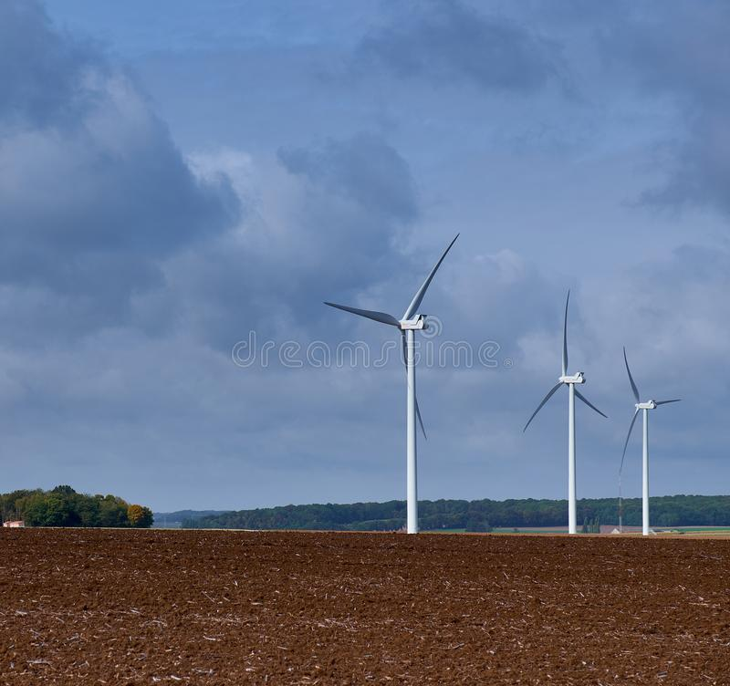 Three wind turbines in a plughed-up field stock images