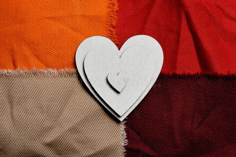 Three white wooden hearts of different sizes on each other. Canvas background composed of four orange and red canvas rectangles.  stock photography