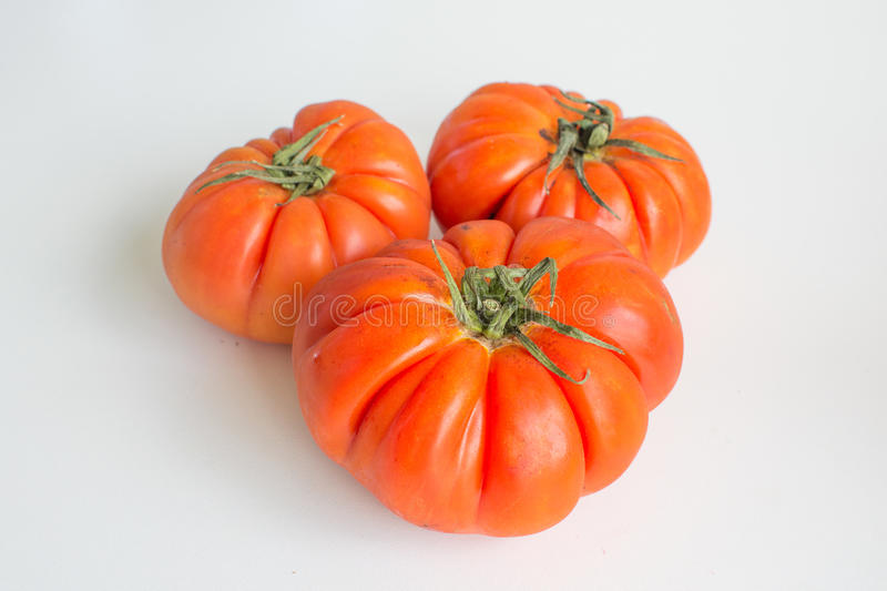 Three whole beefsteak tomatoes stock images