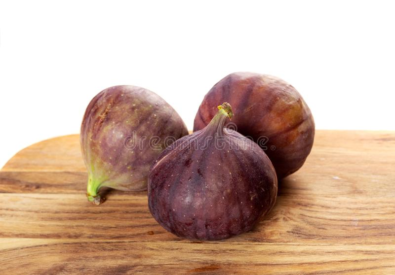 Three whole figs fruits on wooden background closeup stock images